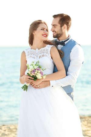 Happy wedding couple on sea beach