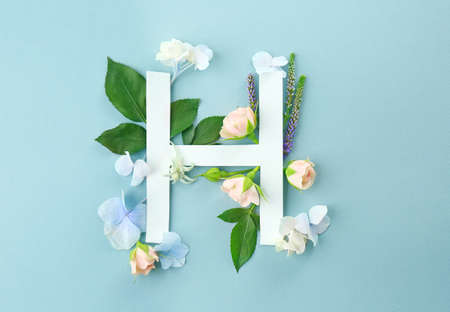 Composition with letter H and beautiful flowers on color background