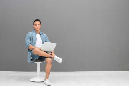 Young man with laptop sitting on chair near grey wall