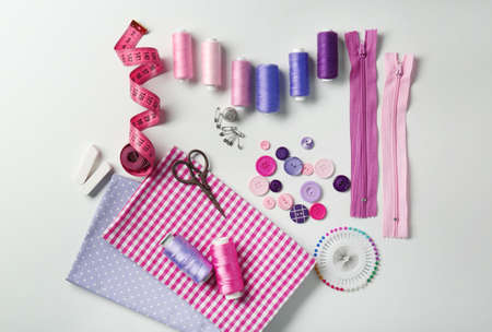 Composition with threads and sewing accessories on white background