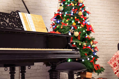 Interior of room with piano and fir tree. Christmas music concept