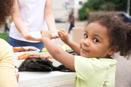 Wolontariusz dzieli się jedzeniem z biednym afrykańskim dzieckiem na świeżym powietrzu