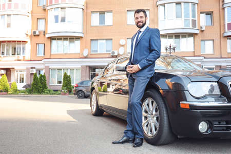Handsome young man in elegant suit standing near car outdoors