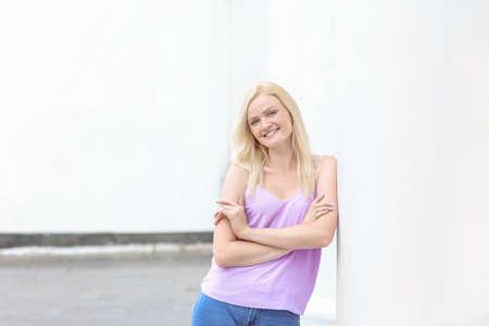Beautiful young woman near column outdoors