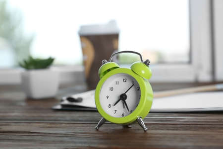 Alarm clock on wooden window sill. Morning routine concept