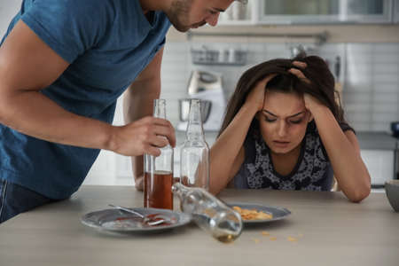 Young woman and drunk man at home Stock Photo