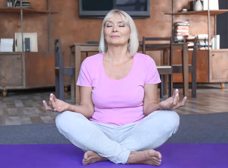 Attractive mature woman meditating at home