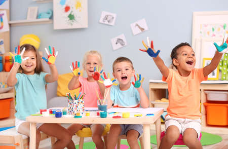 Cute children with painted palms at table indoor