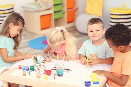 Enfants mignons, peinture à table à l'intérieur