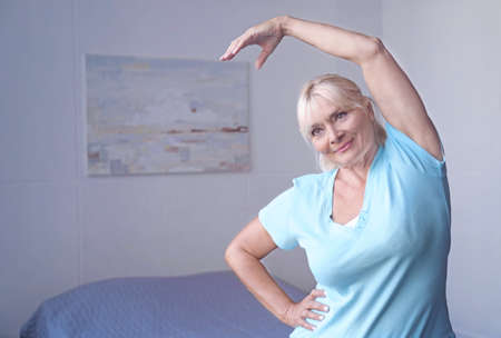 Attractive mature woman exercising at home