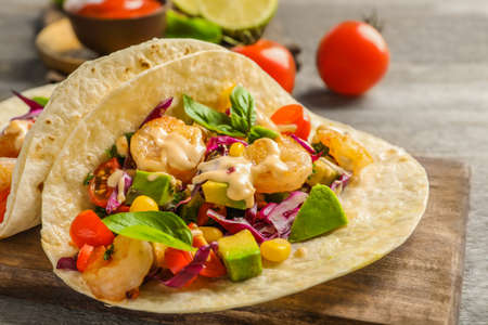Board with delicious shrimp tacos on wooden table