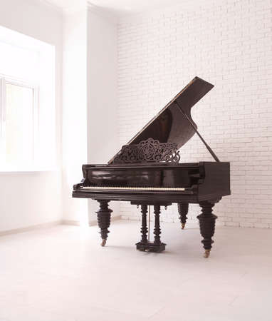 Grand piano with raised lid near brick wall