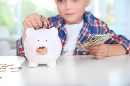 Cute little boy putting coin into piggy bank indoors