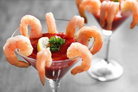 Glass with shrimp cocktail and tomato sauce on table, closeup