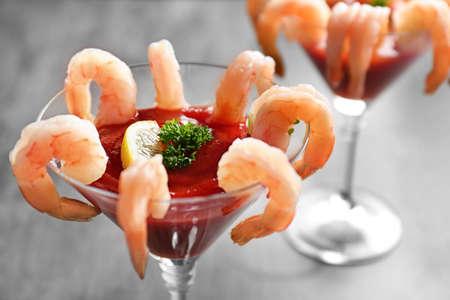 Verre avec cocktail de crevettes et sauce tomate sur table, gros plan