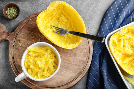 Cup with flesh of spaghetti squash on wooden board