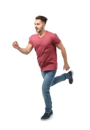 Young man in casual clothes running against white background Stock Photo