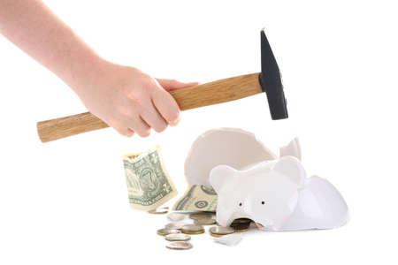Woman holding hammer near broken piggy bank on white background