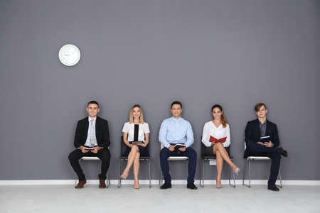 Group of people waiting for job interview on gray wall background Zdjęcie Seryjne