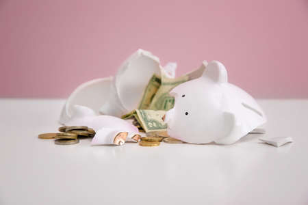 Broken piggy bank with money on white table against color background