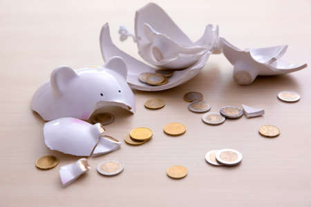 Broken piggy bank with coins on light background