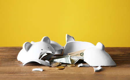 Broken piggy bank with money on wooden table against color background
