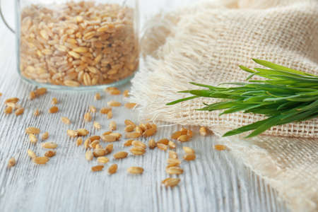 Scattered seeds and wheat grass on wooden table Stock Photo