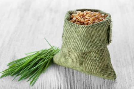 Bag with seeds and wheat grass on wooden table