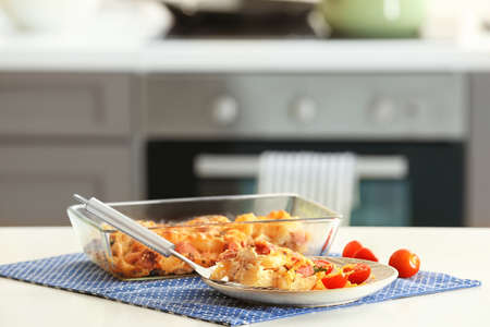 Delicious sausage casserole in kitchenware on table
