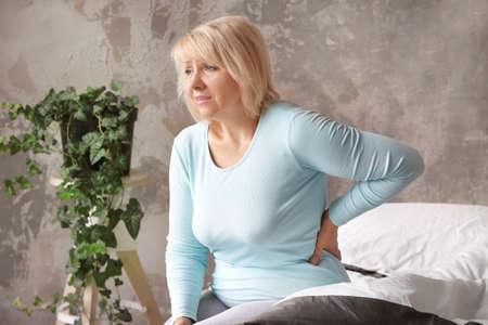 Mature woman suffering from backache at home 免版税图像
