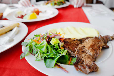 Plate with tasty mashed potatoes, fried meat and salad on table, closeup