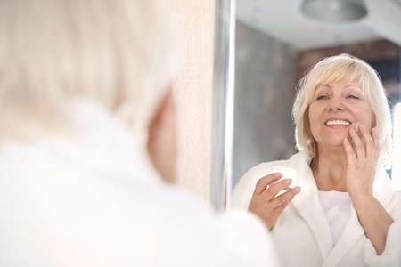 Mature woman applying anti-aging cream at home