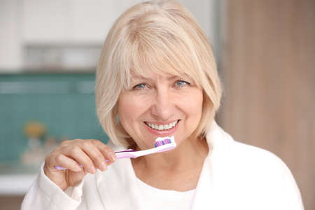 Mature woman cleaning teeth at home