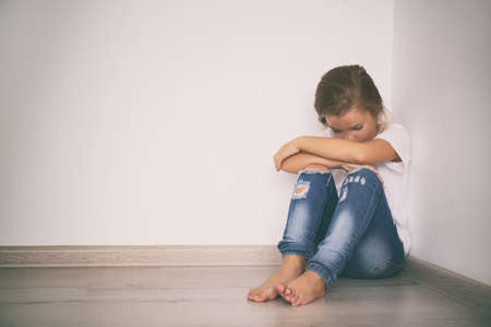 Scared little girl sitting in corner. Domestic violence concept