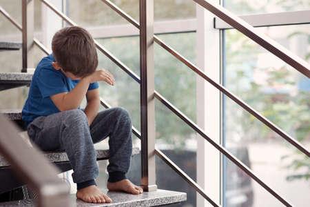 Kleine jongen huilen op trappen binnenshuis. Huiselijk geweld concept