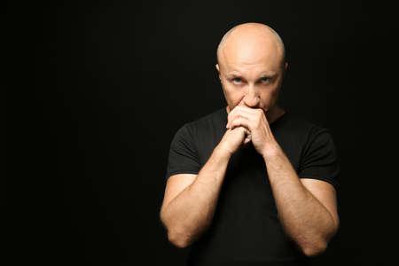 Bald man in t-shirt on black background