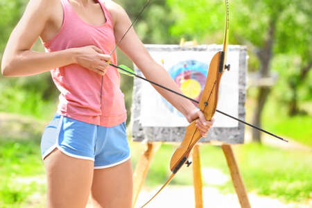 Young woman practicing archery outdoors Stock Photo