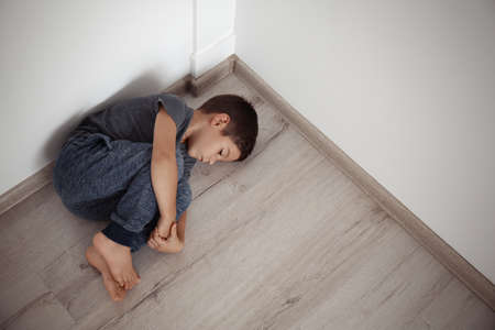 Little boy lying on floor in corner of room. Domestic violence concept