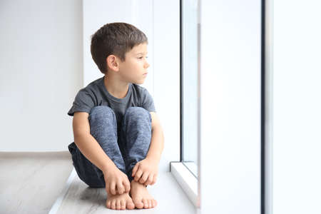 Little boy sitting on windowsill. Domestic violence concept