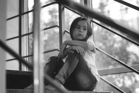 Little girl sitting on stairs indoors. Domestic violence concept