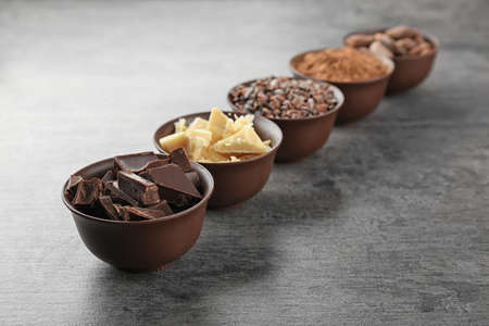 Bowls with cocoa products on grey background
