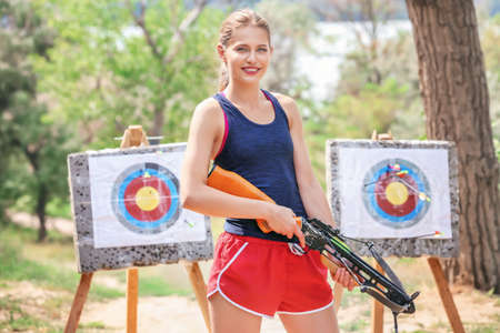 Young woman shooting crossbow outdoors
