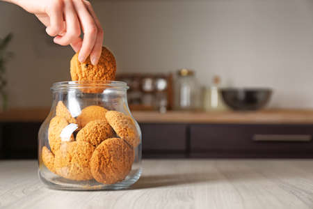 Woman taking oatmeal cookie from glass jar