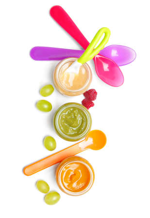 Jars with different baby food and spoons on white background