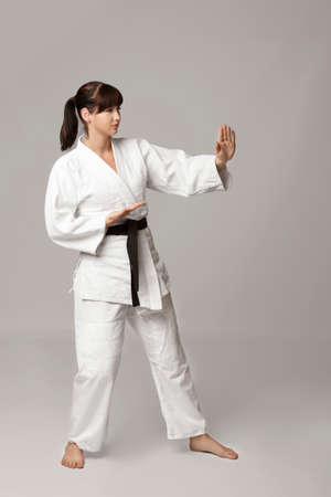 Young woman practicing karate on light background