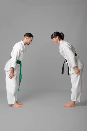 Young man and woman performing ritual bow prior to practicing karate on light background