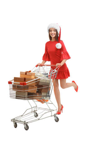 Young woman in Santa hat with gifts in shopping cart on white background. Boxing day concept Stock Photo