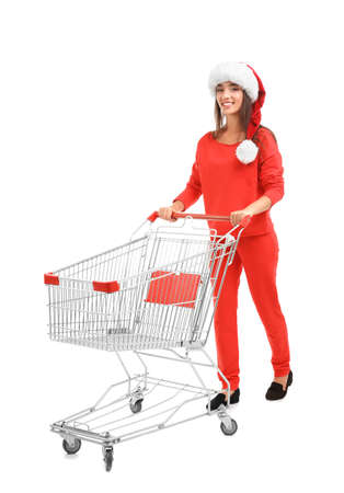 Young woman in Santa hat with  shopping cart on white background. Boxing day concept