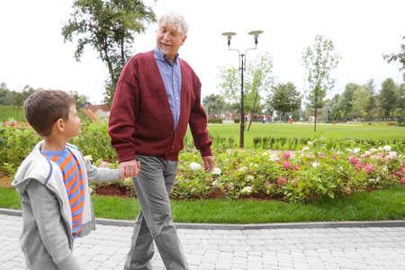 Happy senior man with grandson in park Standard-Bild
