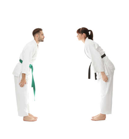 Young man and woman performing ritual bow prior to practicing karate on white background